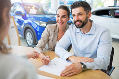 Couple with car dealer in auto salon. Young couple with car dealer in auto salon Stock Photography