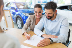 Couple with car dealer in auto salon. Young couple with car dealer in auto salon Royalty Free Stock Photo
