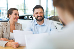 Couple with car dealer in auto salon. Young couple with car dealer in auto salon Stock Photos