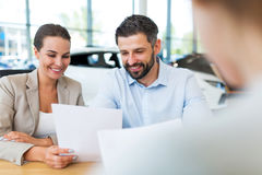 Couple with car dealer in auto salon. Young couple with car dealer in auto salon Stock Image