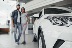 Couple at car dealership. Happy beautiful couple is choosing a new car at dealership Stock Images