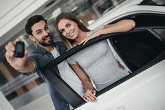 Couple at car dealership. Happy beautiful couple is choosing a new car at dealership, smiling and looking at camera with keys in hand Stock Images