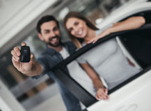 Couple at car dealership. Happy beautiful couple is choosing a new car at dealership, smiling and looking at camera with keys in hand Stock Image