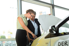 Couple in car dealership looking under  a hood. Woman buying a car in dealership looking under the hood at the engine Stock Photography
