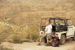 Couple By Car Looking At Desert From Cliff Stock Image