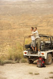 Couple By Car Looking At Desert From Cliff Royalty Free Stock Images