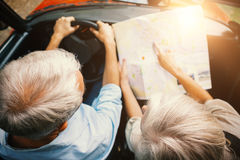 Couple in a car looking at a road map Royalty Free Stock Images
