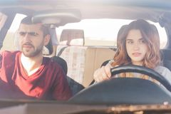 Couple in car on road trip: concentrated experienced female driver sits at wheel and her husband at front passanger seat, look in. Window with focused dreamy Royalty Free Stock Photo