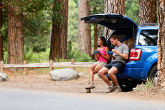 Couple on car road trip travel in eating in forest. Having lunch break outdoors smiling happy. Multiracial couple, Asian woman, Caucasian men People in Yosemite Royalty Free Stock Photography