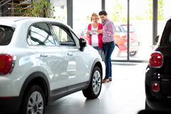 Couple  in car showroom reading brochure Royalty Free Stock Photos