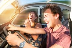 Driving fast. Couple in a car at sunset, with male driving fast and girl scared, screaming and praying Royalty Free Stock Image