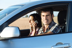 Couple on car travel. Couple on summer car roadtrip. Casual men driving and women talking on cellphone Stock Photos