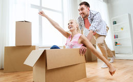 Couple with cardboard boxes having fun at new home Stock Photography
