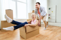 Couple with cardboard boxes having fun at new home royalty free stock images