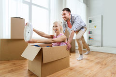 Couple with cardboard boxes having fun at new home Royalty Free Stock Photography
