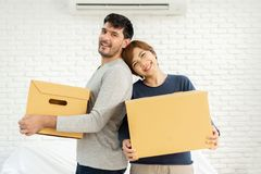 Couple with cardboard boxes at new home. Happy Young Couple with cardboard boxes at new home. Moving house. Looking at camera stock image