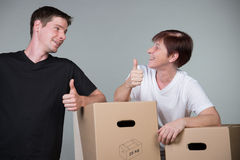 Couple beside cardboards with thumbs up symbol Royalty Free Stock Photo