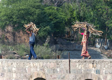 Couple carries firewood on head over bridge in Orchha, India. Royalty Free Stock Photography