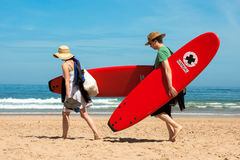 A couple carries surfboards on the beach of Cordoama Royalty Free Stock Photos