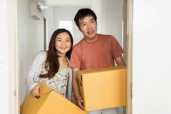Couple carry box to move to new house. Portrait of Happy Asian couple carry cardboard boxes to move stuffs to new house. Wife and Husband moving to new empty Stock Photography