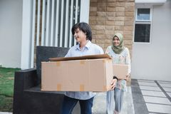 Couple carry cardboard box moving to new house. Happy muslim couple carry cardboard box moving to new house Stock Photos