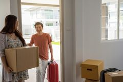 Couple carry moving boxes and luggage to new house royalty free stock image