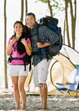 Couple carrying backpacks at campsite Stock Image