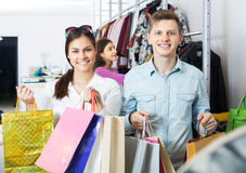 Couple carrying bags in boutique. Positive young couple together carrying bags with purchases and smiling in boutique Stock Photography