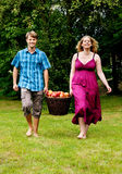 Couple carrying basket with apples Royalty Free Stock Images