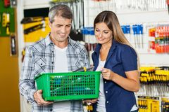Couple Carrying Basket Full Of Tools In Store Stock Photography