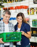 Couple Carrying Basket Full Of Tools In Store Stock Photo