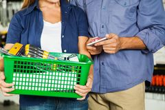 Couple Carrying Basket Full Of Tools In Store Royalty Free Stock Image