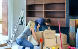 Couple carrying big moving box. In their new home Stock Images