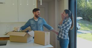 Couple carrying boxes into new home on moving day. Couple carrying boxes into new home on moving day stock footage