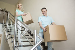 Couple carrying cardboard boxes while moving down steps at new home Royalty Free Stock Photos