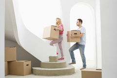 Couple carrying cardboard boxes up stairs in new house Royalty Free Stock Photos