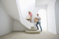 Couple carrying cardboard boxes up stairs in new house Royalty Free Stock Photo