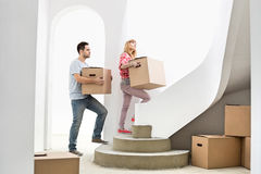 Couple carrying cardboard boxes up stairs in new house Stock Photography