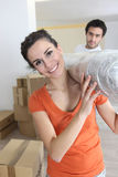 Couple carrying a carpet Stock Image