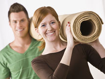 Couple Carrying Carpet Roll Stock Photography