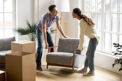 Couple carrying chair together, placing furniture moving in new. Smiling couple carrying modern chair together placing furniture moving into new home, young Stock Photos