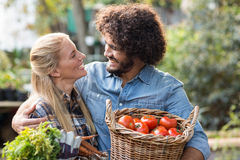 Couple carrying fresh vegetables outside greenhouse Royalty Free Stock Photography