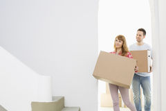 Couple carrying moving boxes Stock Photography