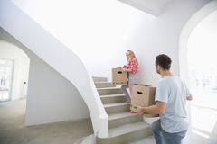 Couple carrying moving boxes up stairs in new house Royalty Free Stock Photo