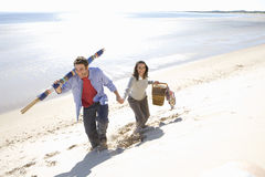 Couple carrying picnic basket and blankets on beach Royalty Free Stock Images