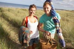 Couple Carrying Picnic Basket Walking Throug. Young Couple Carrying Picnic Basket And Windbreak Walking Through Dunes at beach Stock Photos