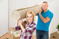 Couple Carrying Rolled Carpet Stock Photos