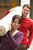 Couple Carrying Rolled Carpet Stock Image