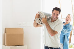 Couple carrying rolled rug after moving in a house Royalty Free Stock Images