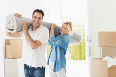Couple carrying rolled rug after moving in a house Stock Photos